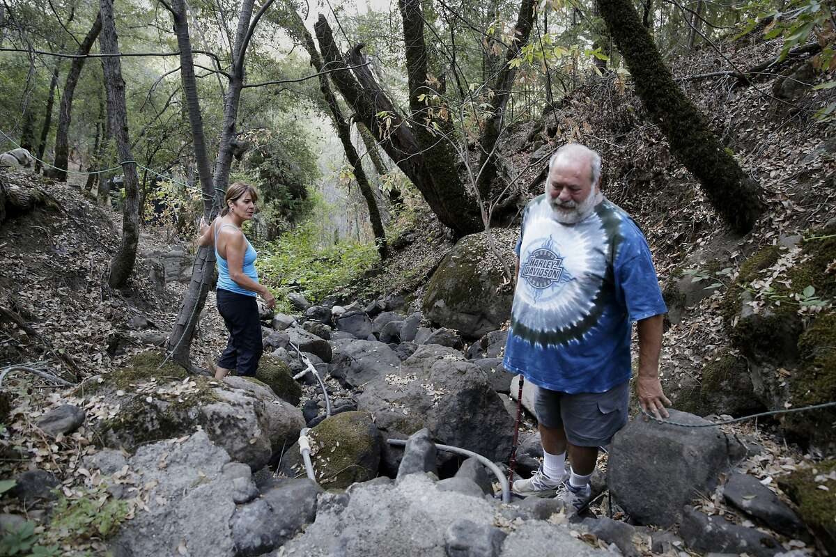 Linda Tucker and her husband, Mark Harzarian, walk a creek on their property that has run dry due to the drought and upstream marijuana grows in Oak Run (Shasta County) on Friday, July 31, 2015.
