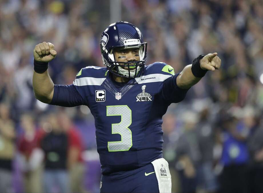 Russell Wilson celebrates after throwing a touchdown pass during the first half of NFL Super Bowl XLIX football game against the New England Patriots in Glendale, Ariz. Russell Wilson is sticking around with the Seattle Seahawks. Wilson tweeted Friday morning, July 31, 2015, that he has agreed to a four-year contract extension with the Seahawks, keeping him with the franchise that took him in the third round of the 2012 draft and watched him become one of the most successful young quarterbacks in NFL history.(AP Photo/David Goldman), File Photo: David Goldman, Associated Press