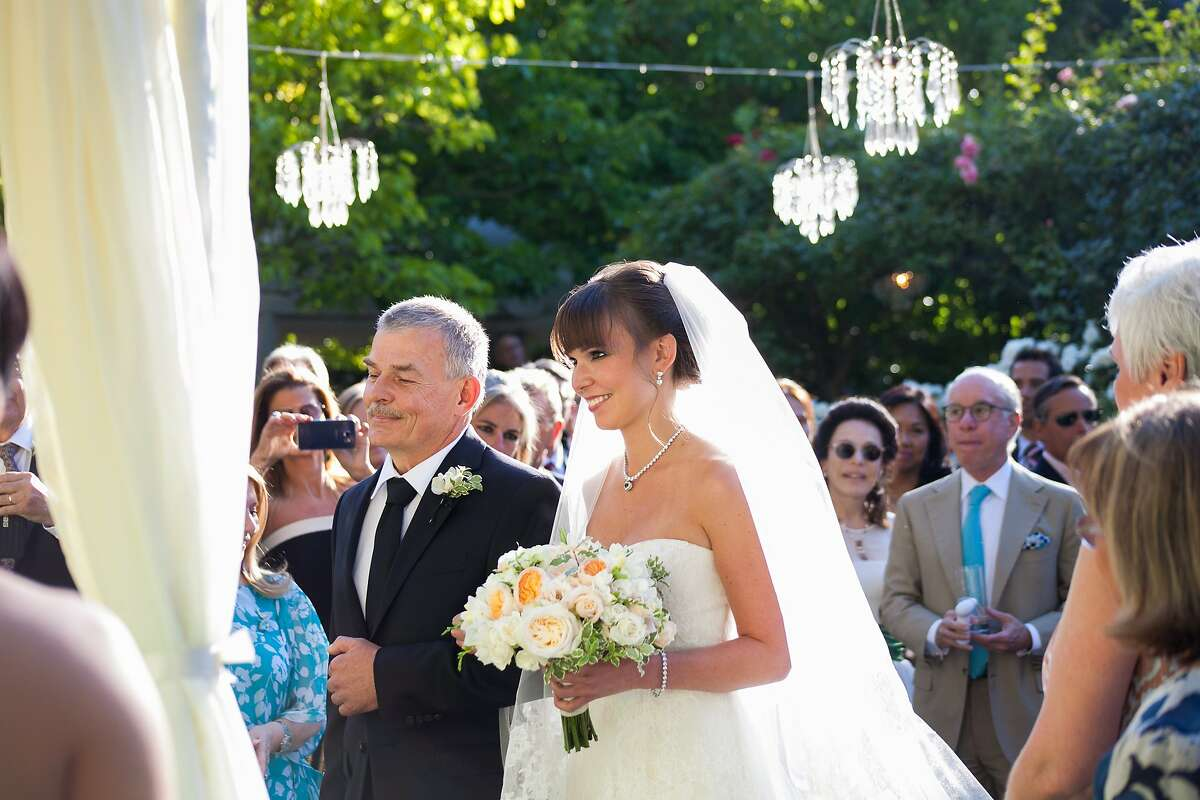 Wine entrepreneurs Serge Troxel and Olya Sadovskaya wed July 15, 2015, in St. Helena, CA, in a ceremony at the home of his mother and stepfather, with a small ensemble of the Russian National Orchestra performing during the reception. Here, the bride heads to the altar with her father, Vasili Sadovski.