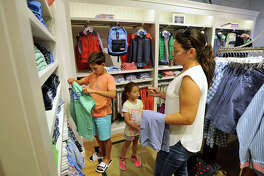 Linda Pagano, of Bronxville, NY, shops with her children Jack, 11, a sixth grader at Bronxville Middle School, and Samantha, 6, a first grader at Bronxville Elementary School, at Vineyard Vines during the start of tax-free week for school shopping in Greenwich, Conn., on Sunday, Aug. 17, 2014. The yearly weeklong cessation of sales tax pertains only to shoes and clothing under $300. Tax-free week ends Saturday, August 23.