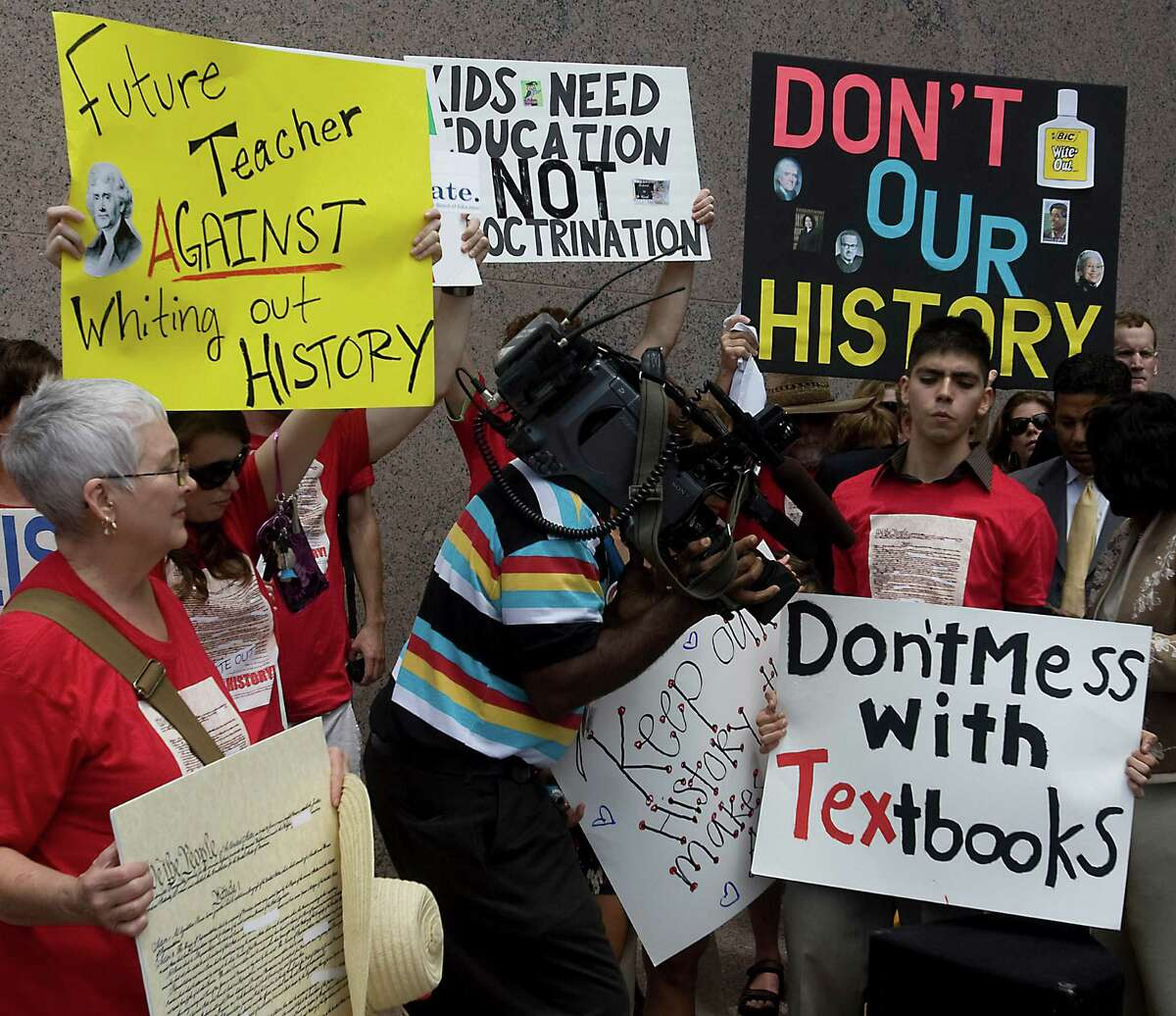 In this 2010 file photo, a member of the media takes close-up video of a protest sign at a rally outside a State Board of Education meeting. The Texas Board of Education approved textbooks with a deeply flawed version of American history.