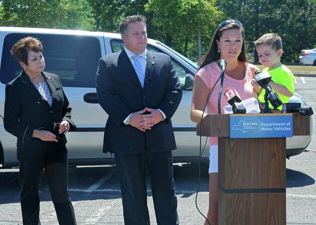 "Leslie Carroll of Cohoes holds her son Matthew, 2, as she speaks during an event to remind parents and caregivers to ""look before you lock"" during National Heatstroke Prevention Day at Colonie Center on Friday, July 31, 2015 in Colonie, N.Y. Carroll has never left a child in the car but more than 30 children in the U.S., including one from New York State, died from heatstroke after being left in a hot vehicle in 2014. Town of Colonie Supervisor Paula Mahan and Albany County Executive Daniel McCoy stand behind her. (Lori Van Buren / Times Union) Photo: Lori Van Buren / 10032849A"