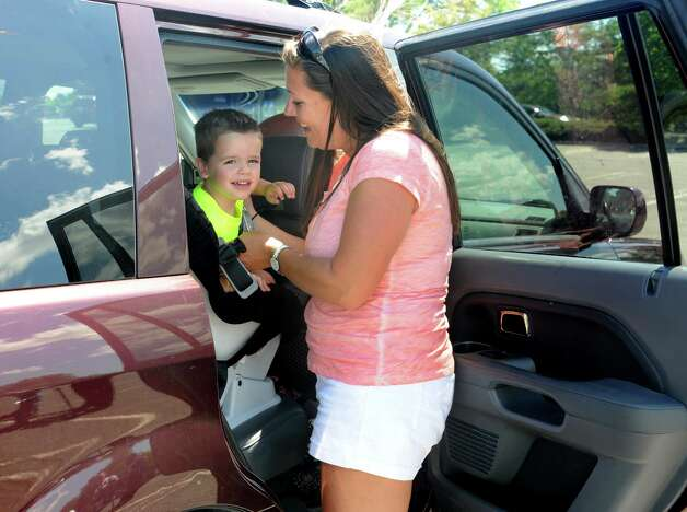 "Leslie Carroll of Cohoes takes her son Matthew, 2, out of her car during an event to remind parents and caregivers to ""look before you lock"" during National Heatstroke Prevention Day at Colonie Center on Friday, July 31, 2015 in Colonie, N.Y. Carroll has never left a child in the car but more than 30 children in the U.S., including one from New York State, died from heatstroke after being left in a hot vehicle in 2014. Carroll always leaves her purse or diaper bag in the bag seat as a reminder. (Lori Van Buren / Times Union) Photo: Lori Van Buren / 10032849A"