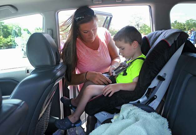 "Leslie Carroll of Cohoes puts her son Matthew, 2, in his car seat during an event to remind parents and caregivers to ""look before you lock"" during National Heatstroke Prevention Day at Colonie Center on Friday, July 31, 2015 in Colonie, N.Y. Carroll has never left a child in the car but more than 30 children in the U.S., including one from New York State, died from heatstroke after being left in a hot vehicle in 2014. Carroll always leaves her purse or diaper bag in the bag seat as a reminder. (Lori Van Buren / Times Union) Photo: Lori Van Buren / 10032849A"