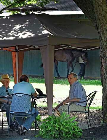 Trainer Carl Domino, right, holds court in the shade of a tree near his barn Friday morning July 31, 2015  at the Saratoga Race Course in Saratoga Springs, N.Y.      (Skip Dickstein/Times Union) Photo: SKIP DICKSTEIN