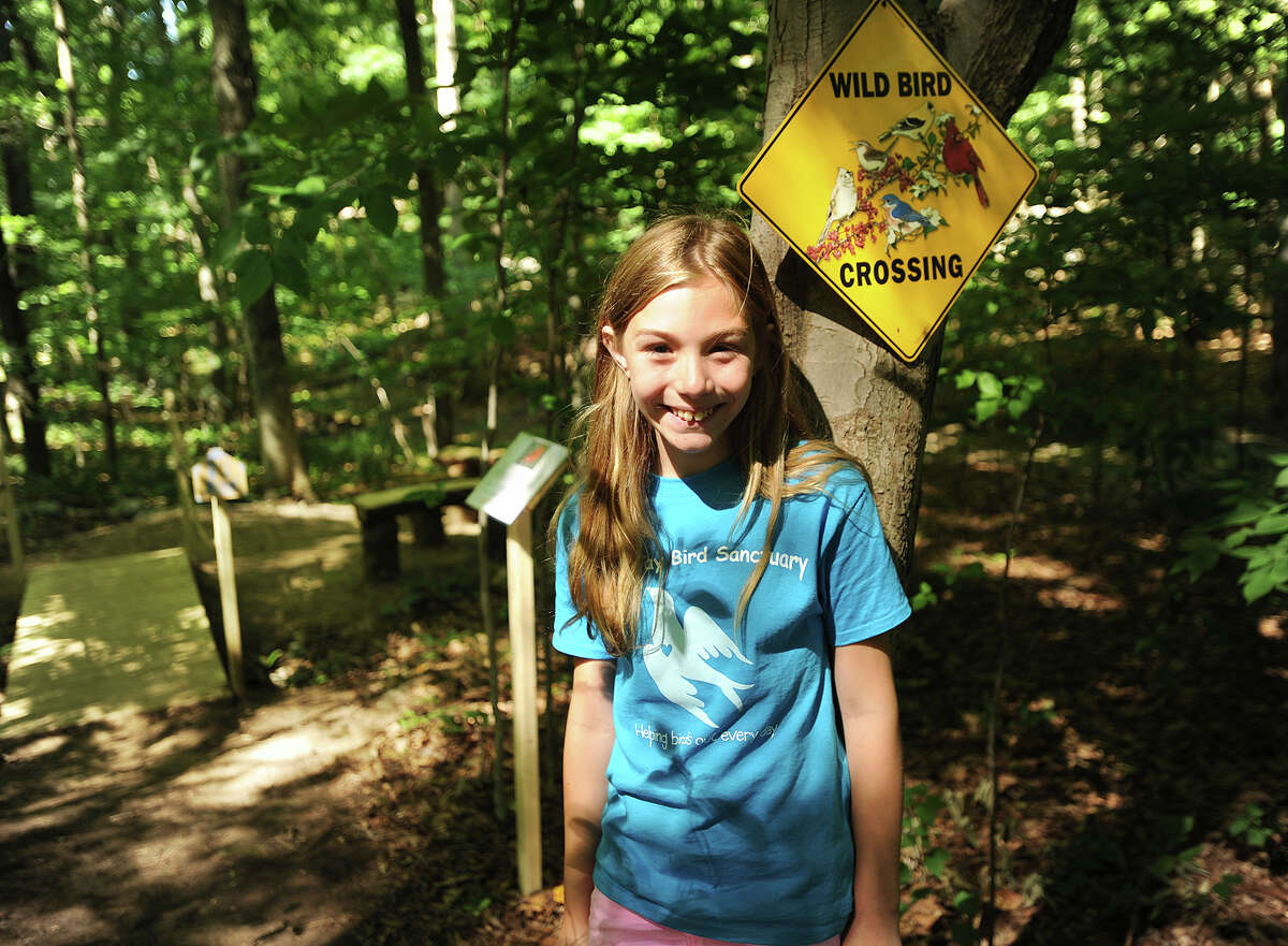 Kaitlyn Lapine, 10, of Monroe, stands in the Blue Jay Bird Sanctuary that she recently constructed with the assistance of friends and family in the woods behind her home in Monroe, Conn. on Thursday, July 23, 2015. The sanctuary includes winding pathways, a wooden bridge, a seating area with a table, and a variety of bird houses and informational displays.