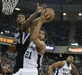 The San Antonio Spurs' Tim Duncan (21) pulls down a rebound ahead of the Sacramento Kings' Jason Thompson in the first quarter on Friday, Feb. 27, 2015, at Sleep Train Arena in Sacramento, Calif. (Jose Luis Villegas/Sacramento Bee/TNS)