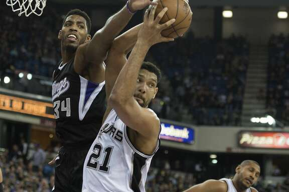 The San Antonio Spurs' Tim Duncan (21) pulls down a rebound ahead of the Sacramento Kings' Jason Thompson in the first quarter on Friday, Feb. 27, 2015, at Sleep Train Arena in Sacramento, Calif. (Jose Luis Villegas/Sacramento Bee/TNS)