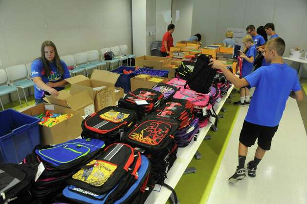 CAP COM Federal Credit Union staff and student volunteers from Shenendehowa High School help the CAP COM Cares Foundation fill nearly 600 backpacks with school supplies on Friday July 31, 2015 in Colonie, N.Y. (Michael P. Farrell/Times Union) Photo: Michael P. Farrell / 00032802A