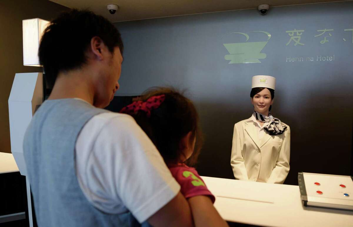 A customer holding a girl, left, looks at a Kokoro Company Ltd. humanoid robot at the reception desk of Henn na Hotel, operated by Huis Ten Bosch Co., a unit of H.I.S. Co., in Sasebo, Nagasaki Prefecture, Japan.