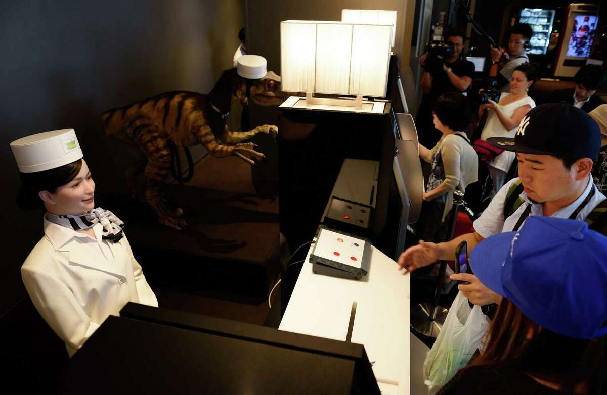 A Kokoro Company Ltd. humanoid robot, left, and a dinosaur robot, second left, stand as customers gather at the reception desk of Henn na Hotel.