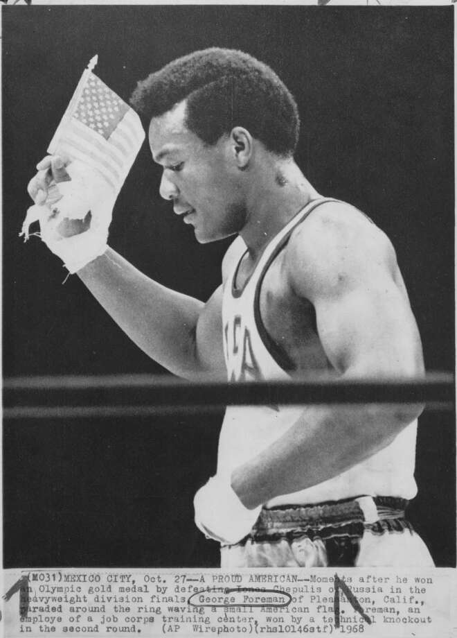 Moments after he won an Olympic gold medal in Mexico City in 1968, George Foreman paraded around the ring waving a small American flag. Photo: Stf / AP Wirephoto
