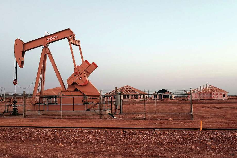An oil well is viewed near a construction site for homes on February 5, 2015 in Midland, Texas. (Photo by Spencer Platt/Getty Images) Photo: Spencer Platt, Staff / 2015 Getty Images