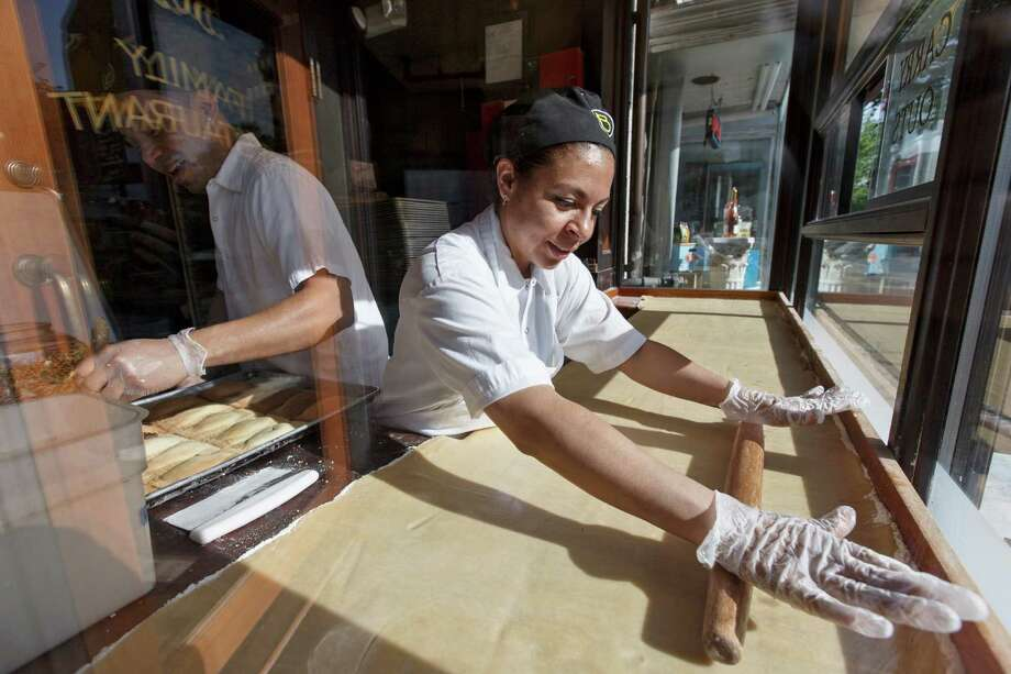 Fatima Godoy rolls out the dough as Gustavo Servellon applies the sprinkles as they make pastries in the bay window at Teds Bulletin, a Capitol Hill restaurant in Washington. The Labor Department reported that salaries and benefits for private sector workers were unchanged during the second quarter. Photo: Associated Press File Photo / AP
