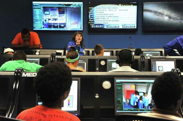 Flight director Julie Muffler helps students from the Rotterdam Boys and Girls Club complete their ground control mission in the Challenger Learning Center at MiSci the museum of innovation and science on Friday July 31, 2015 in Schenectady, N.Y. (Michael P. Farrell/Times Union) Photo: Michael P. Farrell / 10032836A