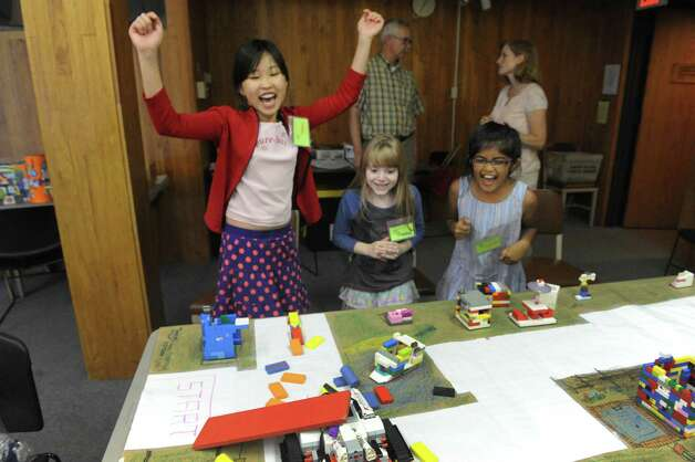 Left to right, Selena Yao, Cadence Graham and Simran Uhurkar cheer as their Lego Robotics machine crahes at MiSci the museum of innovation and science on Friday July 31, 2015 in Schenectady, N.Y. (Michael P. Farrell/Times Union) Photo: Michael P. Farrell / 10032836A