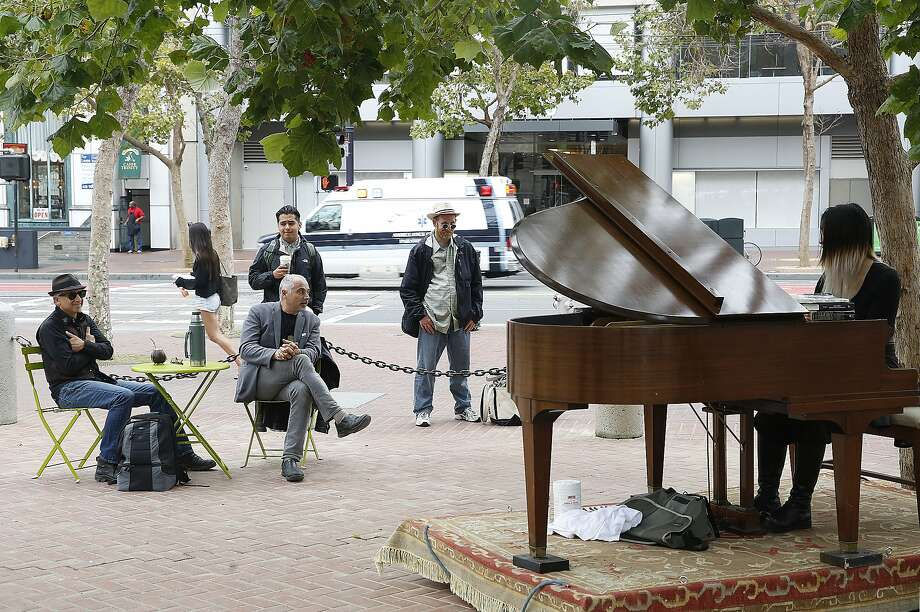 Artist and director Dean Mermell (wearing hat at far left) and artist Mauro ffortissimo (middle seated at green table, last name spelt with lowercase f's) listen to musician Serene Han (far right) play the grand piano at the U.N. Plaza in San Francisco, Calif., on Friday, July 31, 2015. Photo: Liz Hafalia, The Chronicle