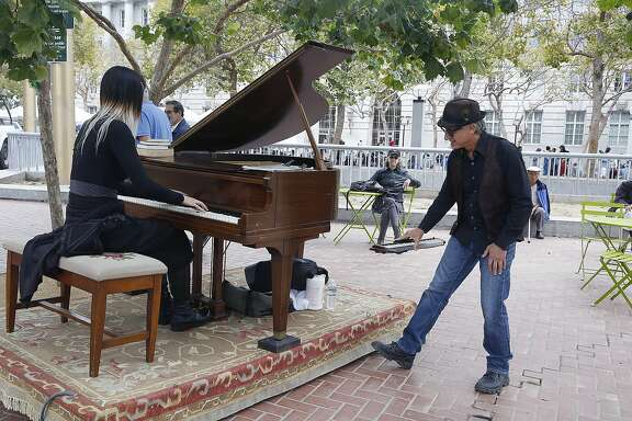 Musican Serene Han (left) plays the grand piano as artist and director Dean Mermell  of Sunset Piano listens at the U.N. Plaza in San Francisco, Calif., on Friday, July 31, 2015.