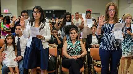 Standing front row left to right: Lizeth Murillo and Saira Lopez take the oath of allegiance during a special naturalization ceremony where the U.S. Citizenship and Immigration Services (USCIS) presented candidates for citizenship to the U.S. District Court of Connecticut. The event was held at the Ferguson Library, Stamford, CT on Friday, July 31, 2015. Lizeth Murillo originally from Mexico now lives in New Britain, CT, and Saira Lopez originally from Columbia now lives in Stamford, CT