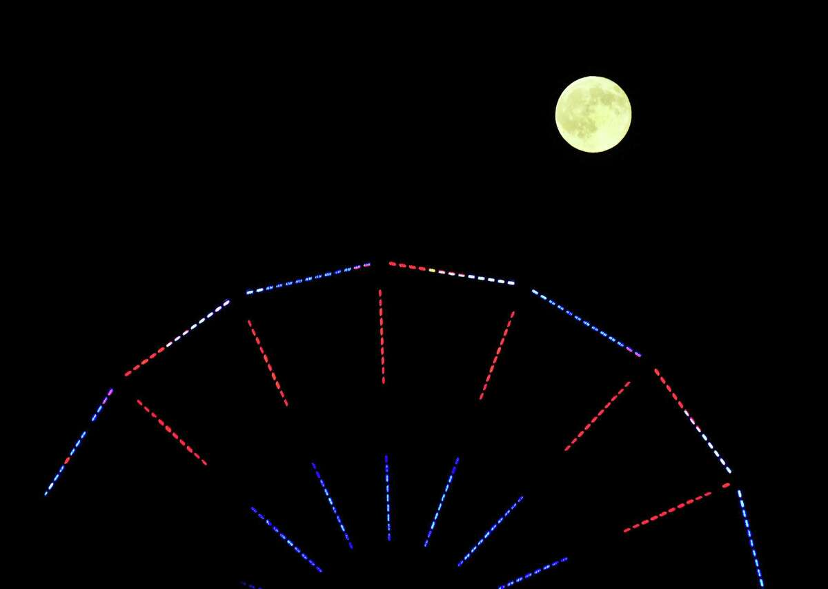 A full moon rises at the 20th Annual Gathering of the Vibes at Seaside Park in Bridgeport, Conn., on Friday July 31, 2015.