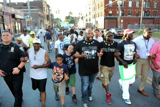 Damonni Farley Sr., center, locks arms with other men as they protest street violence on Friday, July 31, 2015, in Schenectady, N.Y.  (Cindy Schultz / Times Union) Photo: Cindy Schultz / 10032832A