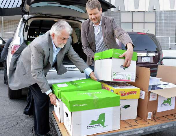 Michael Newell, left, COO of Empire State Health Solutions and Dr. Kyle Kingsley, Founder and CEO of Empire State Health Solutions load cases of license application documents for a proposed medical Marijuana production facility being delivered to the Bureau of Narcotic Enforcement New York State Department of Health Thursday June 4, 2015 in Albany, NY. (John Carl D'Annibale / Times Union) Photo: John Carl D'Annibale / 00032158A