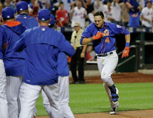 New York Mets' Wilmer Flores (4) approaches home plate and awaiting teammates after hitting a walk off solo home run during the twelfth inning of a baseball game to beat the Washington Nationals 2-1, Friday, July 31, 2015, in New York. (AP Photo/Julie Jacobson)  ORG XMIT: NYJJ124 Photo: Julie Jacobson / AP