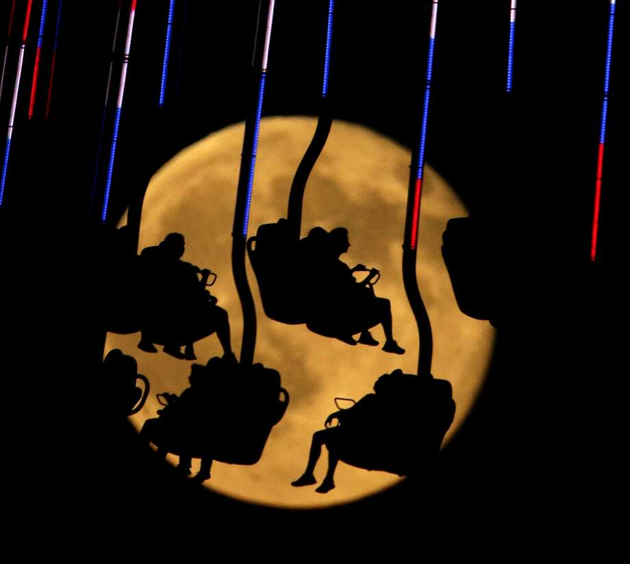 People are silhouetted against a rising blue moon as they ride an attraction at Worlds of Fun amusement park camp Friday, July 31, 2015, in Kansas City, Mo.  A blue moon happens when the moon rises in its full stage twice during the same month. Photo: Charlie Riedel, Associated Press