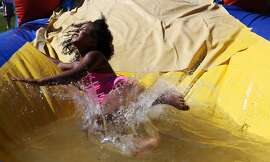 Children play at an inflatable water slide during the 11th annual back-to-school bash at the John B. Hughes apartments in Springfield, Mo., Friday, July 31, 2015. (Guillermo Hernandez Martinez/The Springfield News-Leader via AP)