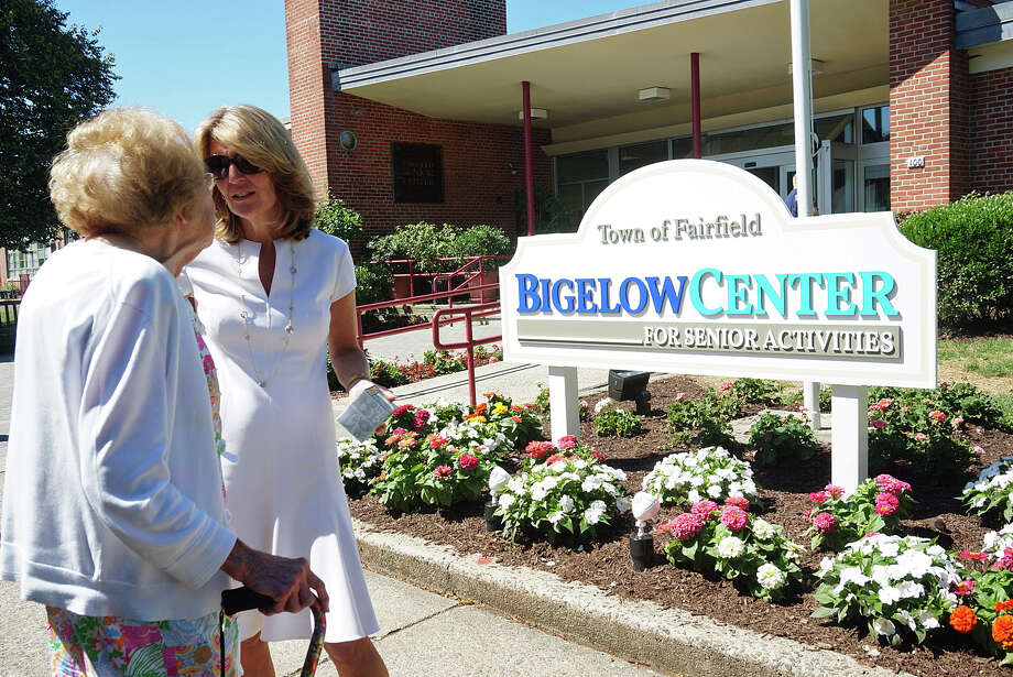 Cindi Bigelow, CEO and president of Bigelow Tea, talks with Janet Gillis in front of the new sign at the town's senior center that was unveiled Friday. Photo: Genevieve Reilly / Genevieve Reilly / Fairfield Citizen