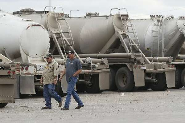 Two men walk past a row of tanker trucks at a gas station in Cotulla, Texas on Thursday, Dec. 11, 2014. The truck stop remained busy as oil production continues in the Eagle Ford region. (Kin Man Hui/San Antonio Express-News)