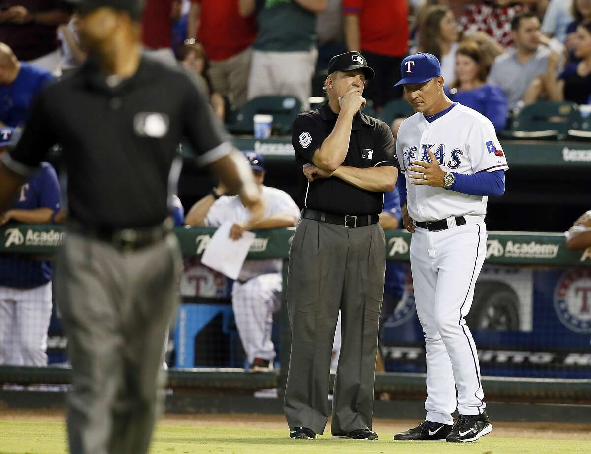 Umpire Jeff Kellogg talks with Texas Rangers manager Jeff Banister after a heated exchange between members of the Rangers and San Francisco Giants starting pitcher Madison Bumgarner in the fourth inning of a baseball game Friday, July 31, 2015, in Arlington, Texas.