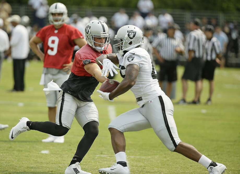 Oakland Raiders quarterback Derek Carr, left, hands off the ball to Marcel Reece, right, during their football training camp Friday, July 31, 2015, in Napa, Calif. (AP Photo/Eric Risberg) Photo: Eric Risberg, Associated Press