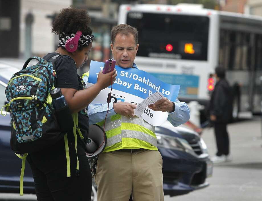 BART public information officer Jim Allison assists a passenger traveling to San Francisco at the 19th Street station in Oakland, Calif. on Saturday, Aug. 1, 2015. BART has arranged for a bus bridge while transbay service is shut down for the weekend to perform major track maintenance between the West Oakland station and the entrance to the tube. Photo: Paul Chinn, The Chronicle