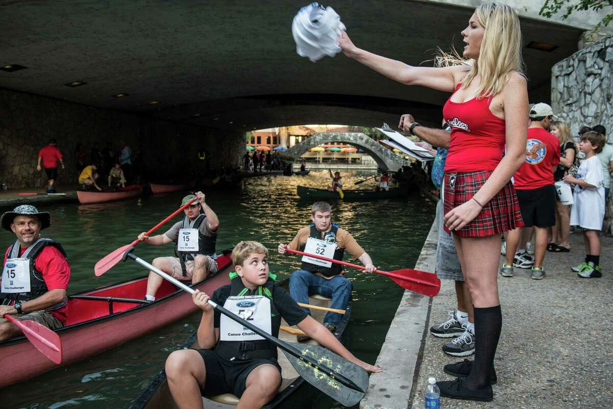 Megan Schwartzkopf, right, the designated flag starter waves the start of a heat during the scout category of the Ford Canoe Challenge on the San Antonio Riverwalk on Saturday, August 1, 2015. The race has been a tradition since 1969.