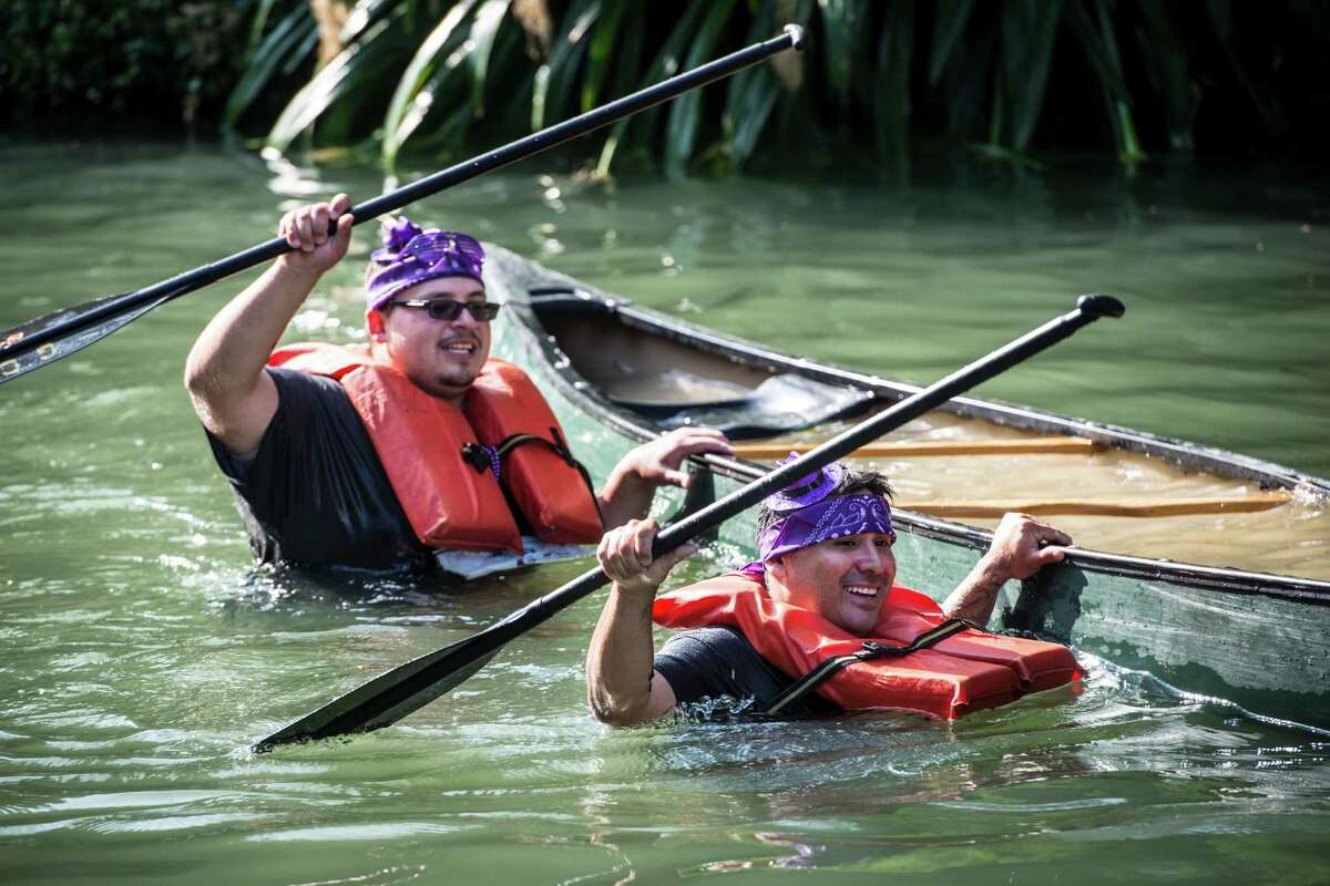 Chris Palomo, left, and Randy Guerra, right, walk their canoe to the finish as the crowded finish cheers them on after tipping over during the Ford Canoe Challenge on the San Antonio Riverwalk on Saturday, August 1, 2015.