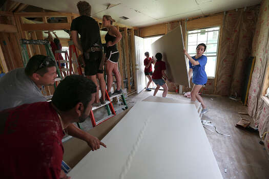 Niki Bordelon, 18, right, of Austin, and other Southern Methodist University Catholic Campus Ministry student volunteers carry plasterboards at Project Azteca in San Juan, Texas, Friday, May 22, 2015. The program provides interest-free home loans to residents of colonias in Hidalgo County. Future homeowners are required to work on the houses that are built on a lot at Project Azteca. After they are finished, the houses are moved to lots in colonias around the county. The program is funded with federal monies. Project Azteca is aiming to build 30 houses this year and has a waiting list of 4,000 families. Photo: JERRY LARA, Staff / San Antonio Express-News / © 2015 San Antonio Express-News