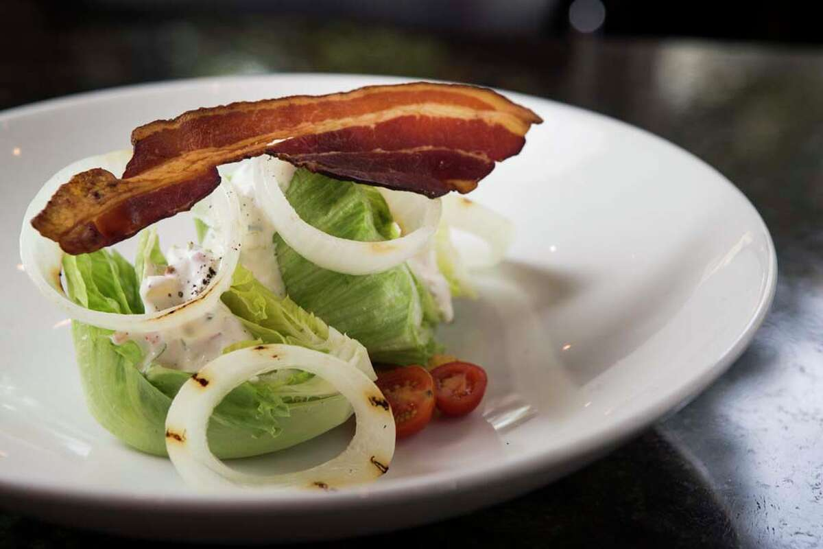 The Wedge Salad, with buttermilk-peppercorn ranch, bacon, grilled onions, tomatoes and fried pkled okra, is shown at Holley's Seafood Restaurant & Oyster Bar.