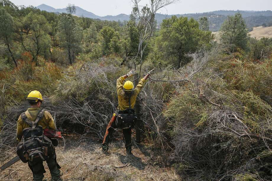Firefighters Cody Morris (left) and Rafael Morales tie up fire lines as part of mop-up work along Morgan Valley Road near Lower Lake. Photo: Loren Elliott, The Chronicle