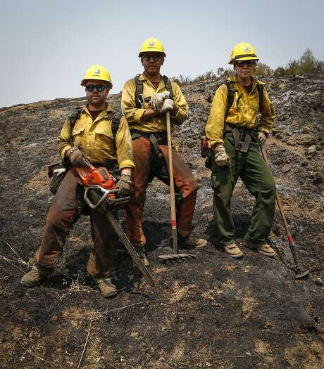 Firefighters Cody Morris (left), Rafael Morales and Shanisa Dove take a short break while working to tie together fire lines near Lower Lake. Photo: Loren Elliott, The Chronicle