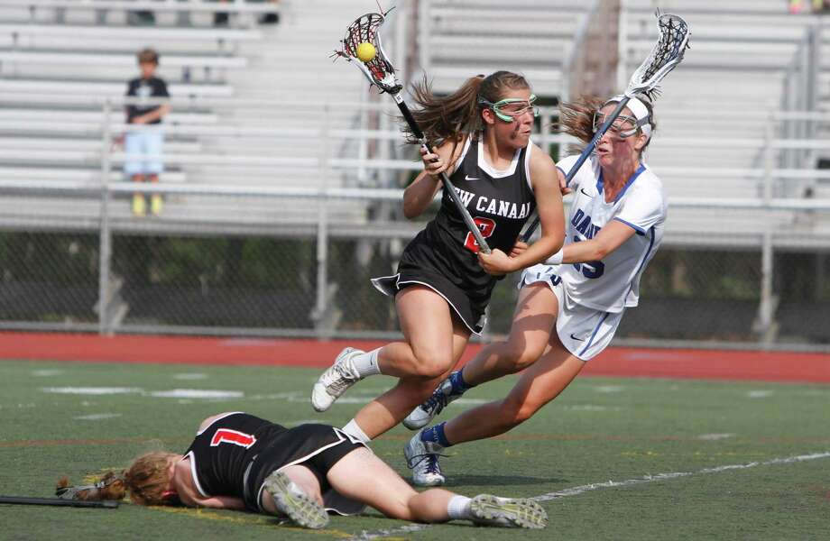 New Canaan's Catherine Granito, center, charges past Darien's Laura Murphy during the FCIAC Girls Lacrosse Championship at Brien McMahon High School in Norwalk, Conn. on Thursday, May 28, 2015. Darien defeated New Canaan 13-12 in triple overtime. Photo: Matthew Brown / Matthew Brown / Connecticut Post Freelance
