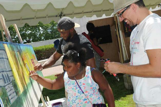 Artist Tony Iadicicco, right, helps seven-year-old Kahmani Steele of Albany add to a painting in progress of the plaza skyline at the Albany Center Gallery satellite art exhibit during the Black Arts and Cultural Festival at the Empire State Plaza on Saturday Aug. 1, 2015 in Albany, N.Y. (Michael P. Farrell/Times Union) Photo: Michael P. Farrell / 10032814A