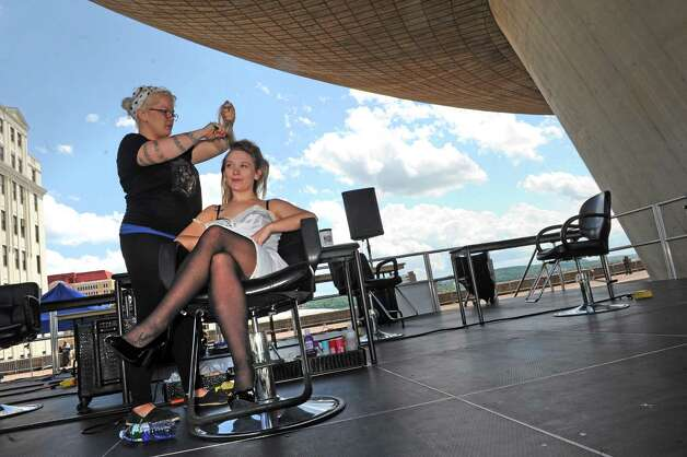 In the shade of the Egg Stylist Shay Francis, left, does the hair of model Abby Andrews in a stylist competition during the Black Arts and Cultural Festival at the Empire State Plaza on Saturday Aug. 1, 2015 in Albany, N.Y. (Michael P. Farrell/Times Union) Photo: Michael P. Farrell / 10032814A