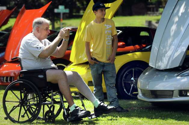 Vietnam veteran Conrad J. Silke of Ulster County, left, takes a picture on Corvette row during the 6th Annual Honor Our Vets Car Show on Saturday, Aug. 1, 2015, at Stratton VA Medical Center in Albany, N.Y. Silke, who was in the Marine Corp., is at the hospital for a knee replacement. (Cindy Schultz / Times Union) Photo: Cindy Schultz / 10032823A