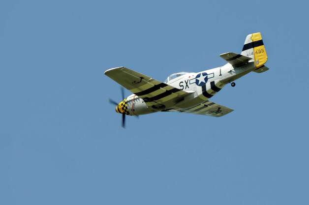The Dallas Doll, left, modeled after the WWII Mustang, does a fly by during the All-Electric Radio Control Model Air Show on Saturday, Aug. 1, 2015, at Maalwyck Park in Glenville, N.Y. Modelers from around the region took part in the event organized by the Electric Powered Aeromodelers Club of Glenville. (Cindy Schultz / Times Union) Photo: Cindy Schultz / 10032822A