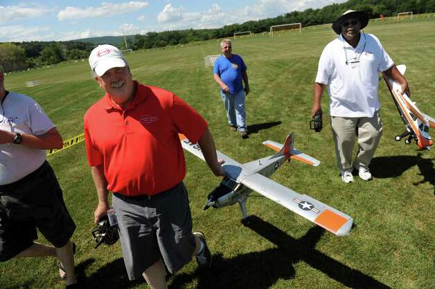 Bill Sawn of Infield, Conn., left, and Phil Jackson of Springfield, Mass., right, carry their Beaver electric-powered aircraft after a flight during the All-Electric Radio Control Model Air Show on Saturday, Aug. 1, 2015, at Maalwyck Park in Glenville, N.Y. Modelers from around the region took part in the event organized by the Electric Powered Aeromodelers Club of Glenville. (Cindy Schultz / Times Union) Photo: Cindy Schultz / 10032822A
