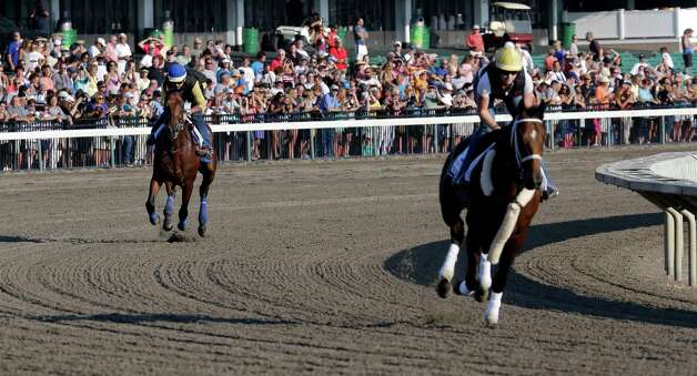 In front of a large crowd of fans, Triple Crown winner American Pharoah, left, with Jorge Alvarez up chases Top Clearance with Calamity Compton up through a turn at Monmouth Park in Oceanport, N.J., Saturday, Aug. 1, 2015, as they train for Sunday's running of the Haskell Invitational horse race. (AP Photo/Mel Evans)   ORG XMIT: NJME104 Photo: Mel Evans / AP