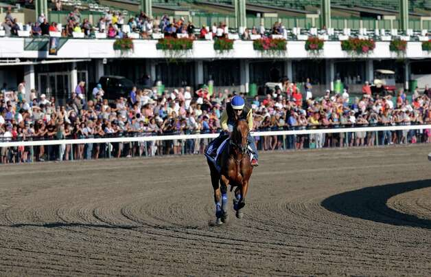 In front of a large crowd of fans, Triple Crown winner American Pharoah with Jorge Alvarez up trains at Monmouth Park in Oceanport, N.J., Saturday, Aug. 1, 2015. American Pharoah is preparing for Sunday's running of the Haskell Invitational horse race. (AP Photo/Mel Evans)    ORG XMIT: NJME107 Photo: Mel Evans / AP