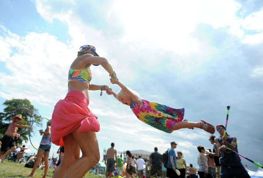 Ashley Szyluk, of West Hartford, swings her three-year-old daughter through the air during the 20th annual Gathering of the Vibes music festival Saturday, Aug. 1, 2015 at Seaside Park in Bridgeport, Conn. Photo: Autumn Driscoll / Hearst Connecticut Media / Connecticut Post freelance