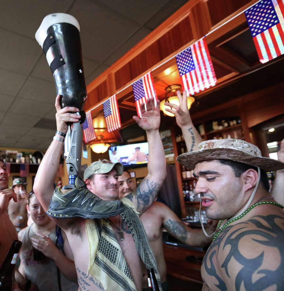 Levi Pope holds up a prosthetic leg after about a dozen veterans drank from it at Pimlico Irish Pub Saturday, Aug. 1, 2015, in Houston. The prosthesis belongs to a veteran who lost his leg to an IED in Afghanistan. The group will travel 22km to raise awareness about PTSD and suicides among veterans, which claim 22 lives each day.